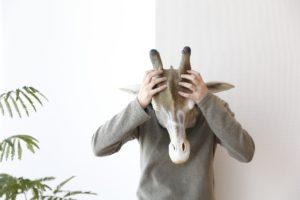 キリンの被り物をして、頭を抱えて悩んでいる男性