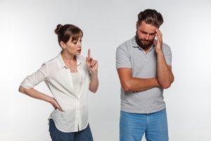 話をしている妻の傍らで、額に手を当てて困った様子の夫