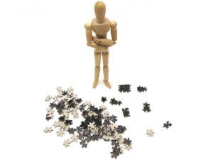 バラバラになったジグソーパズルの前で腕組をして考えている様子の木の人形
