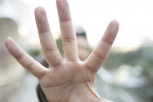 手のひらを前に突き出して拒否の意思を示している男性
