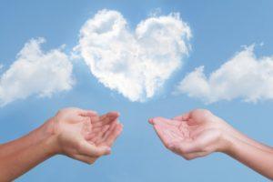 ハートの形をした白い雲の下で水を汲むように両手を差し出している男女