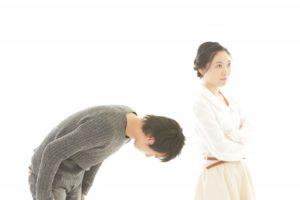 背を向ける妻に頭を深く下げて謝る夫