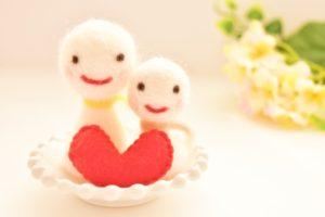 ご機嫌そうに微笑んで赤いハートの後ろに並んでいる、フェルト生地で作られた2体の人形