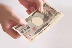 人の手から差し出されている数枚の一万円札