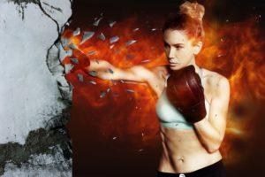 ボクシングの恰好で、目の前の岩盤をパンチで打ち砕いている女性
