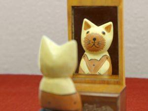 鏡の前に座っている猫の置物